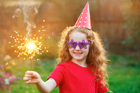 Happy girl in party hat with burning sparkler in her hand. Creative invitation for party, holiday, wedding, birthday, christmas, New Year concept.