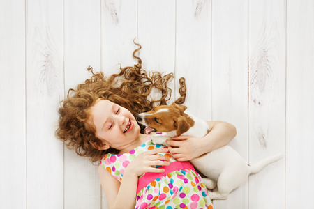Little girl and her friend puppy playing on wooden floor background.