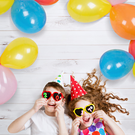 New Years 2017, christmas holiday. Funny children with sunglasses, hold 2017 candles, lies on the wooden floor. High top view. Stock Photo