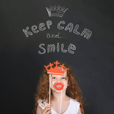 Funny girl with carnival crown and lips showing her teeth, standing beside chalkboard. Keep calm and smile. Happy childhood, healthy smile concept.