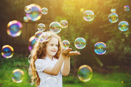 Funny little girl catching soap bubbles in the summer on nature.
