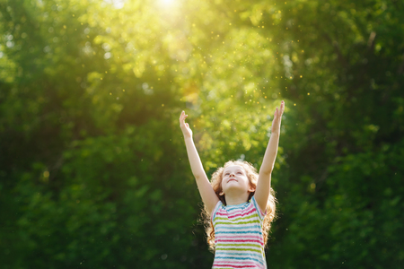 Cute little girl stretches her hand to catch sun rays. Religion, donation, people, charity, happy childhood, peace world concept. Standard-Bild
