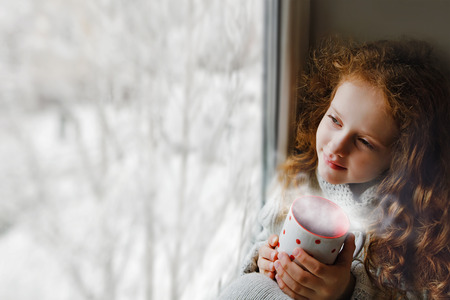 Cute little girl sitting with a cup of hot cocoa by the window and looking on first falling snow through glass early Christmas morning.