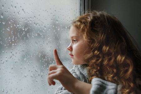 Sad little girl looking out the window on rain drops through wet glass autumn bad weather.