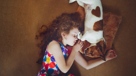 Cute girl hugging a puppy and sleeping on warm wooden floor.