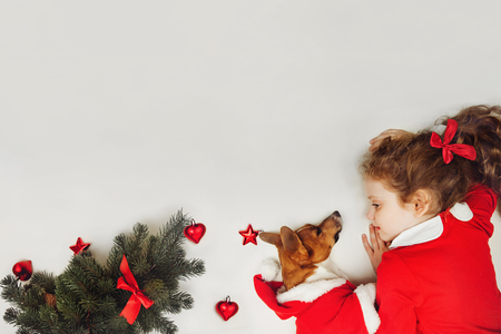 Little girl embracing puppy dog. Holiday concept, Christmas, New year background. High top view. Place of your text.