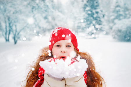 respiration: Little girl blows snow with mittens, on a snowflakes bokeh background.