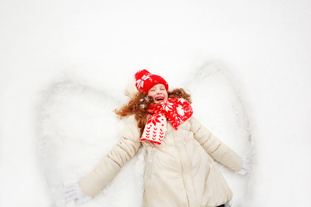 games hand: Laughing girl  laying on a snow moving her hand up and down, playing games winter outdoors. Little girl on a snow showing  angel figures. Stock Photo