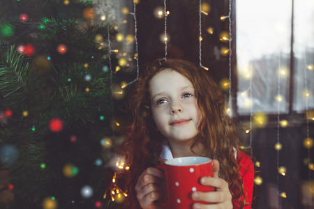 christmas morning: Cute little girl sitting with a cup of hot cocoa by window and looking through glass early Christmas morning.