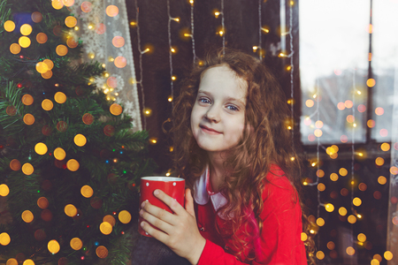 hot drink: Beautiful child girl sitting with a cup of coffee by window and looking through glass in holiday Christmas night.
