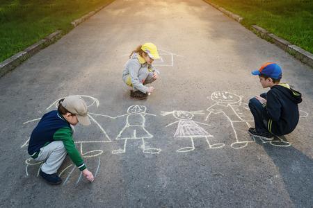 kids outside: Children is drawing happy family on asphalt in spring park.