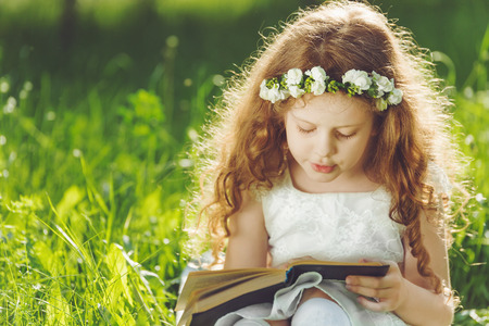 Little girl closed her eyes, praying, dreaming or reading a book in the outdoors.