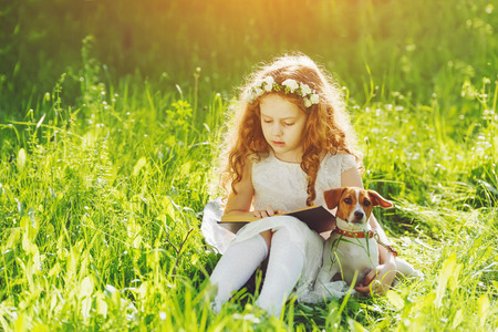 kid book: Little girl reading a book with her friend puppy dog in the outdoors.