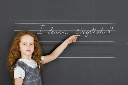 english girl: Schoolgirl says and pointing on chalkboard text I learn English. Education concept.