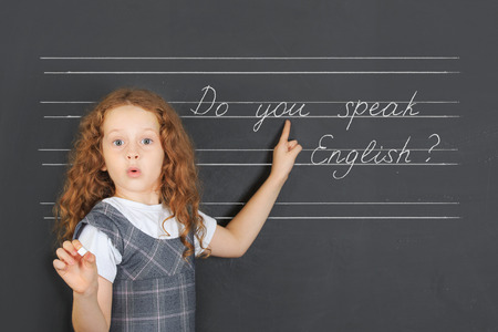 Surprised redhead girl asks a question -  Do you speak English, stand near blackboard in the classroom. Education concept. Stock Photo