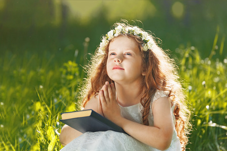 Little girl folded her hand with praying, dreaming in park outdoors.