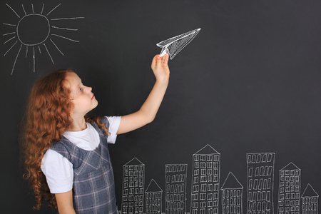 Cute girl throwing paper airplane near blackboard. Happy childhood, education, travel, vacation concept. Imagens