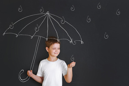 Handsome boy under chalk drawing umbrella, held out his hand and catches the raindrops. Childhood, fantasy and dreaming concept.