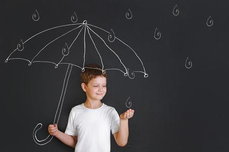Muchacho hermoso dibujo de tiza bajo el paraguas, le tendió la mano y atrapa las gotas de lluvia. La infancia, la fantasía y el sueño concepto. Foto de archivo