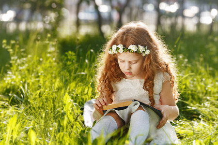 novel: Little curly girl praying, dreaming or reading a book in the outdoors.