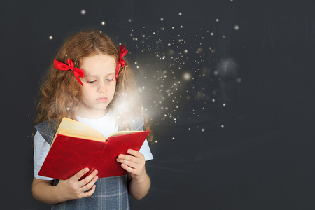 quietly: Little girl reading the book. Education concept. Stock Photo