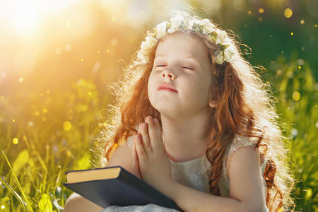 close your eyes: Little girl folded her hand and close your eyes in praying, dreaming in park outdoors.