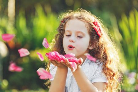 불고 어린 소녀는 그녀의 손에서 장미 꽃잎. 신선한, 건강 호흡 개념입니다.