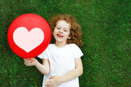 芝生の上に横たわる赤バルーンを保持している白い t シャツの女の子。お母さんのお父さんのバレンタインの概念。