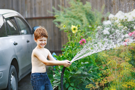 Laughing little boy watering flowers from a garden hose.