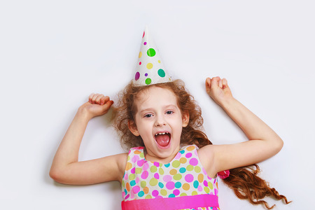 Laughing curly girl in carnival party hat, lying on a light background with high top view. Happy childhood concept.