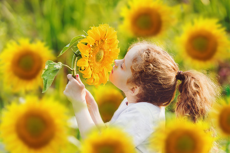 Redhead curly girl with sunflower, enjoying nature outdoor. Healthcare, freedom, peace and happy childhood concept. Stock Photo