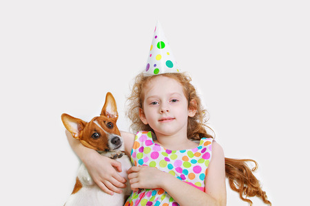 Little girl is smiling and embracing her friend pet, lying on light background. Happy holiday and childhood concept.