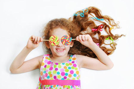 Laughing child with candy lollipop eyes in white background. High top view. Stock Photo