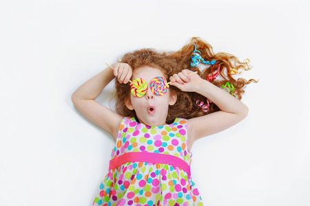 Surprised funny girl  hold candy lollipop on eyes. Child with high top view lying on light background.
