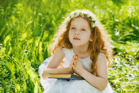 Little girl praying or dreaming  in the park outdoors. Stock Photo