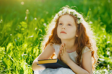Little girl praying or dreaming in the park outdoors.