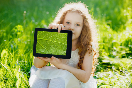 Child holds a tablet PC with a green leaf and studying biology in the park.