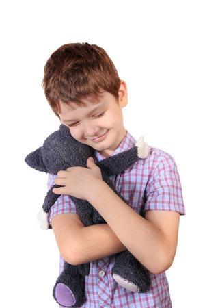 Little boy hugging a toy cat.