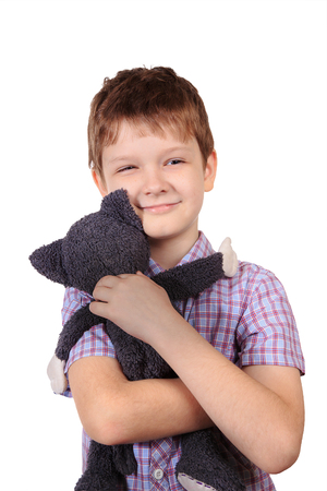 Little boy hugging a toy cat isolated in white background.