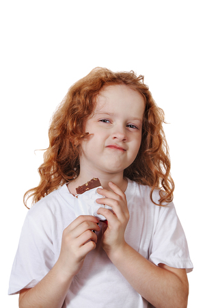 Cute little girl with greedily holding chocolate on a white background.