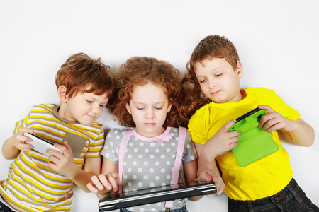 Angry children friend firmly holds his smartphone, notebooks. Dependence medical concept.