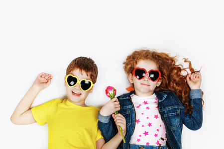 Funny children in sunglasses a heart shape, hold tulips and lies on the light floor. High top view background. Mother, Father or Valentines day concept.