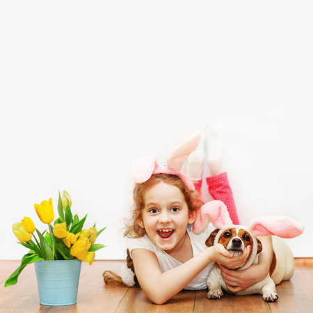 Laughing girl and her friend dog with bunny ears sit on wooden floor on light wall background.