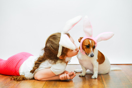 Cute girl and her friend dog with bunny ears sit on wooden floor on  light wall background.