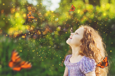 Child with a butterfly on his nose. Fairy dreams for princess girl. Happy childhood concept. Reklamní fotografie