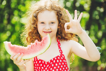 all ok: girl shows gesture ok and eating watermelon. Diet, vitamins, healthy food concept.