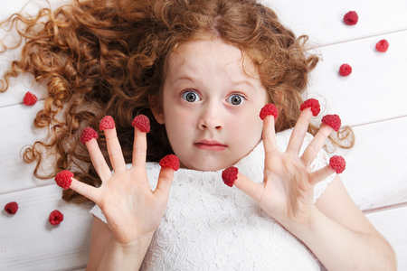 allergic foods: Cute girl with raspberries on her fingers