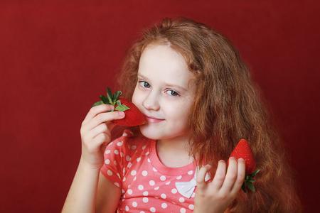 peu drôle fille mange fraise savoureuse, sur fond rouge.