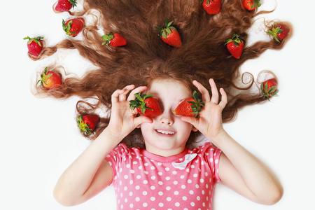 Belle petite fille aux yeux fraises. concept de mode de vie sain.