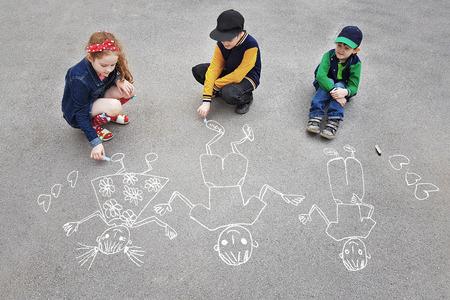 Les enfants se dessinent soleil sur l'asphalte dans le parc de printemps. Banque d'images - 79558770
